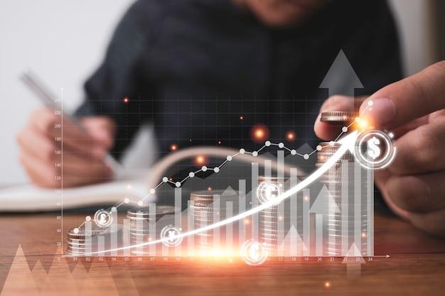 Uomo d'affari che mette le monete che impilano con il grafico virtuale e la freccia di aumento davanti all'uomo d'affari. investimento aziendale e concetto di profitto di risparmio.