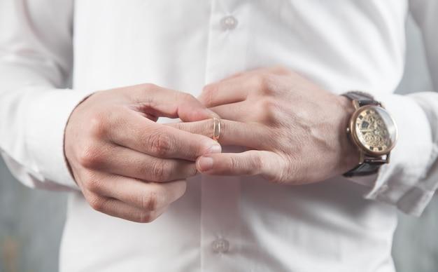 Uomo d'affari che mette il suo anello di nozze.