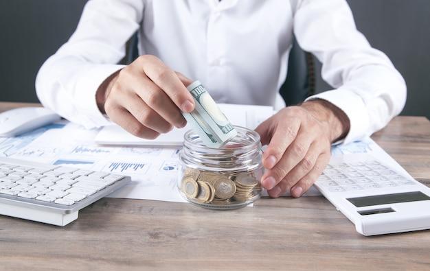 Uomo d'affari che mette soldi in banca di vetro. risparmiare soldi