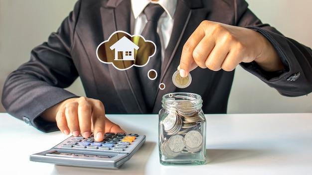 Uomo d'affari che mette soldi in un barattolo di risparmio, idea di risparmio di denaro per comprare una casa.
