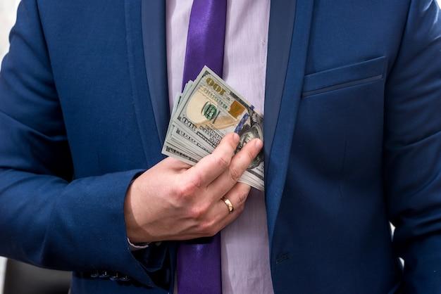 Uomo d'affari che ci mette soldi nella tasca del vestito suit