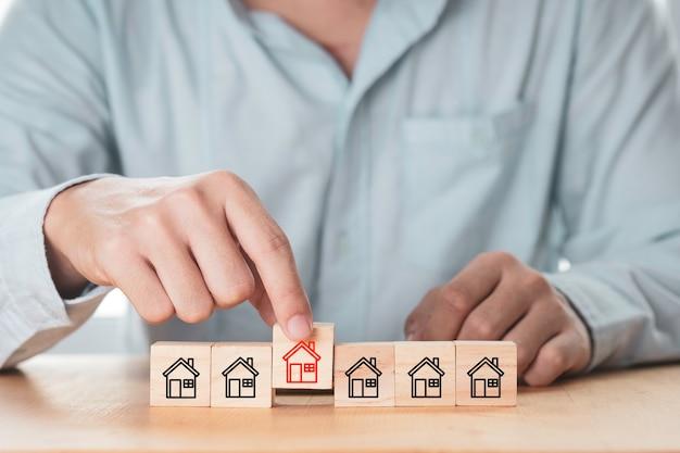 Uomo d'affari che mette il blocco di cubi di legno che stampa lo schermo rosso e la casa bianca per la casa selezionata.