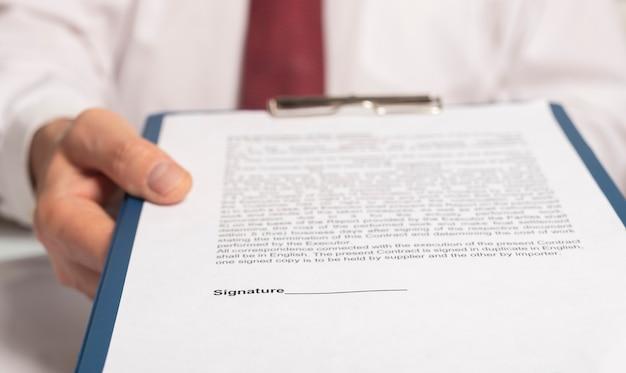 Uomo d'affari che raggiunge i documenti alla fotocamera e si offre di firmarli