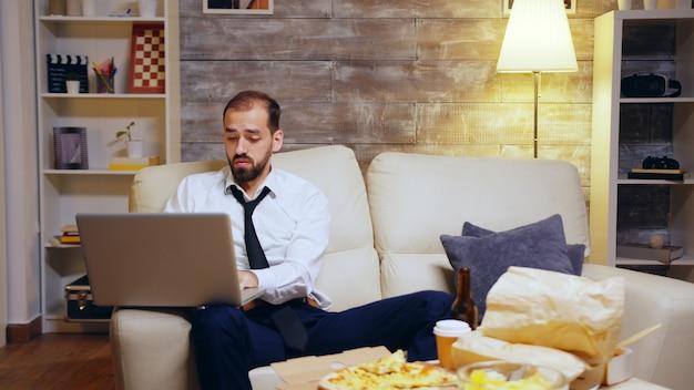 Uomo d'affari che cerca la sua birra mentre lavora al computer portatile da casa. imprenditore in tuta.