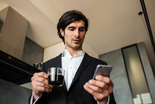 L'uomo d'affari legge le notizie dallo smartphone mentre beve un caffè a casa