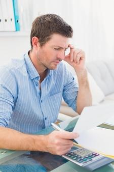 Documento di lettura dell'uomo d'affari alla sua scrivania nel suo ufficio