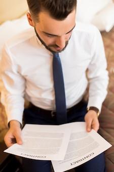 Uomo d'affari reading documents in camera da letto