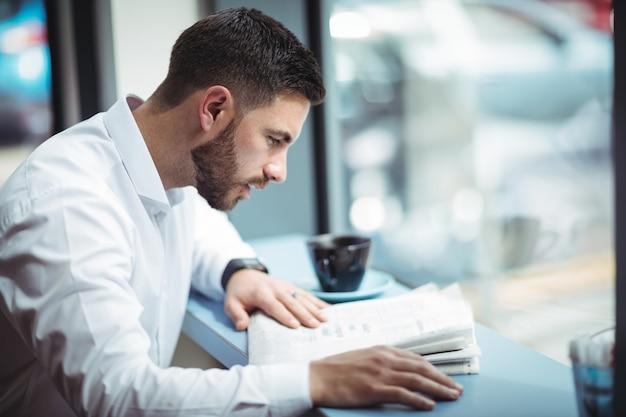 Giornale della lettura dell'uomo d'affari in ufficio