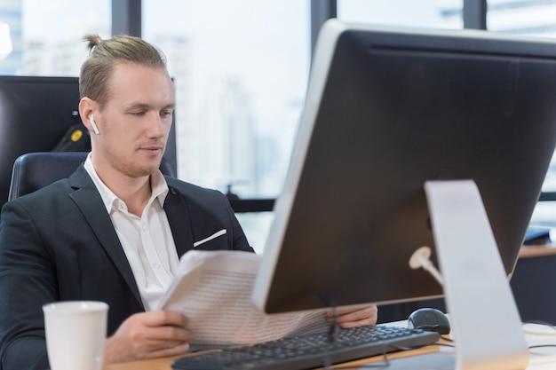 Giornale della lettura dell'uomo d'affari all'ufficio Foto Premium