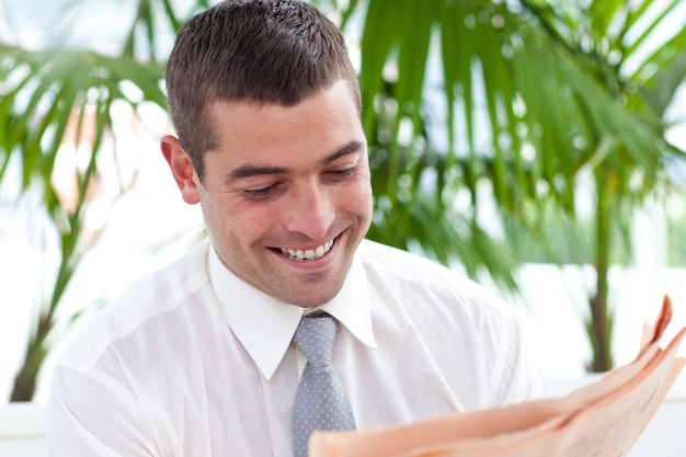 Uomo d'affari che legge un giornale sul posto di lavoro