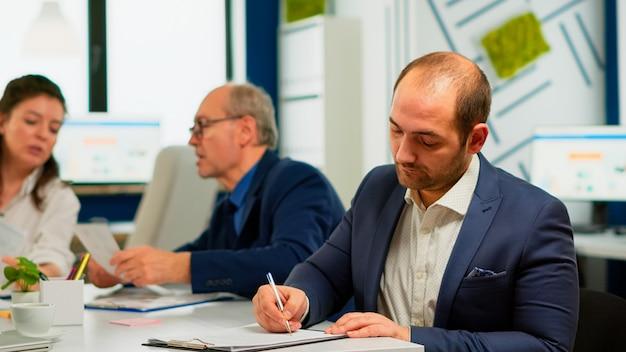 Uomo d'affari che legge un documento cartaceo, discute del contratto con un partner fiducioso, firma documenti di investimento. direttore esecutivo che incontra gli azionisti in carica di avvio, prendendo un accordo soddisfacente.