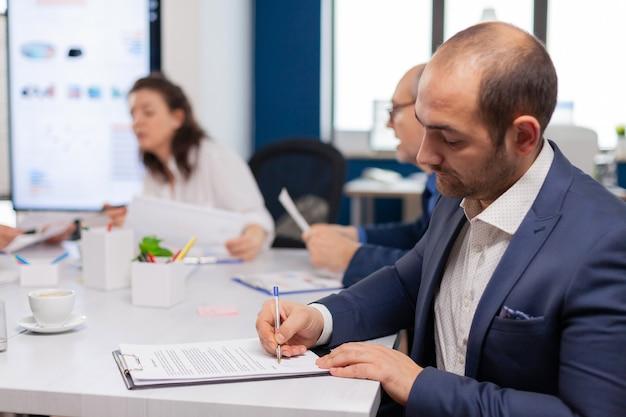 Uomo d'affari che legge un documento cartaceo, discute del contratto con un partner fiducioso, firma documenti di investimento