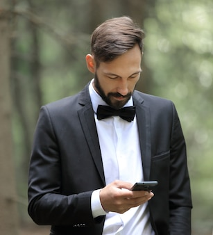 Uomo d'affari che legge sms sullo smartphone in piedi nel bosco.