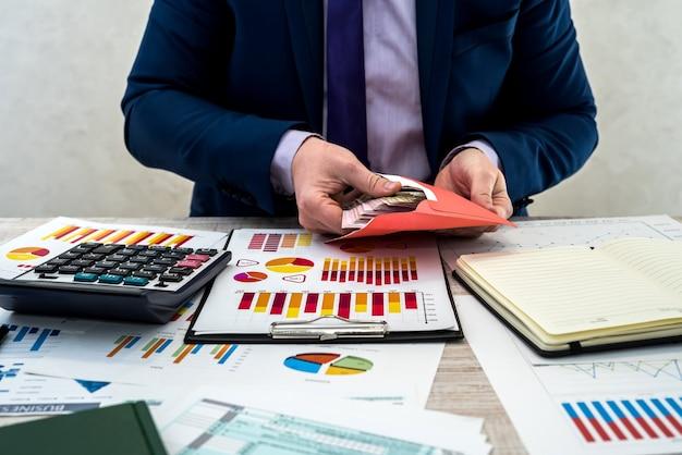 L'uomo d'affari riceve un reddito nascosto in una busta dall'azienda. un uomo lavora con un programma di lavoro e mantiene un profitto in ufficio. il concetto di paga o corruzione.