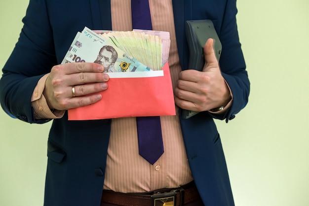 L'uomo d'affari riceve denaro come tangente in busta. un uomo dà un sacco di soldi ucraini grivna in una busta