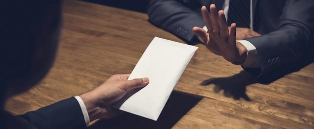 Uomo d'affari che rifiuta soldi in busta bianca offerta dal suo partner nel concetto scuro e anti di corruzione