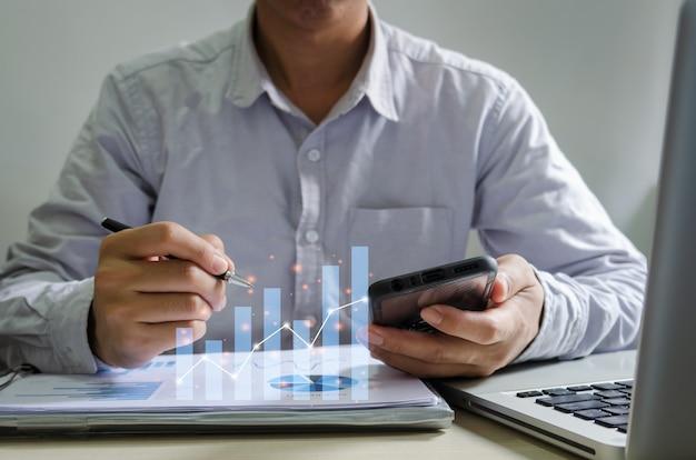 Imprenditore report grafici e tabelle di rendiconti finanziari e crescita dei profitti in possesso di una penna e un telefono cellulare allo scrittorio.