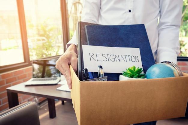 Dimissioni di imprenditore imballando tutti i suoi effetti personali e file in una scatola di cartone marrone