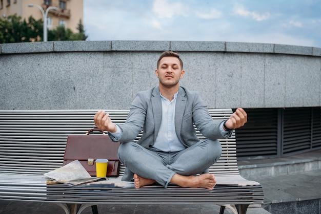 Uomo d'affari che riposa nella posa di yoga sulla panchina presso l'edificio per uffici nel centro cittadino. persona di affari che guida sul trasporto ecologico sulla strada della città, in stile urbano
