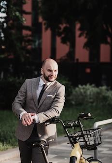 Bicicletta di guida dell'uomo d'affari per lavorare sulla via urbana. concetto di affari. concetto di stile di vita.