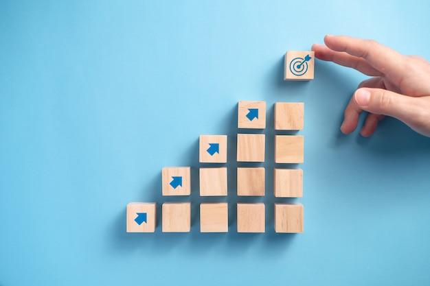 Mano dell'uomo d'affari che organizza la scala dei blocchi di legno con l'icona della freccia, concetto di pianificazione aziendale.