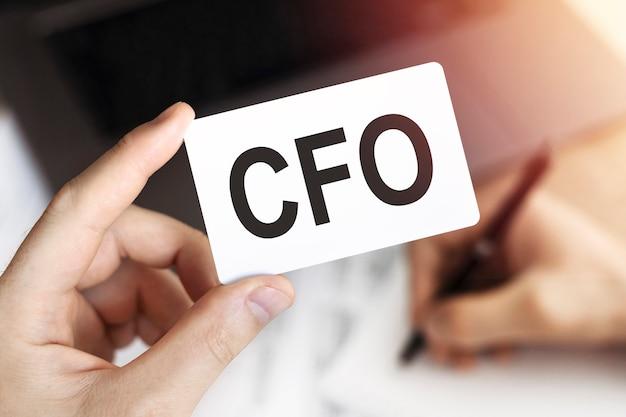 La mano dell'uomo d'affari che tiene una carta con le lettere cfo - chief financial officer.