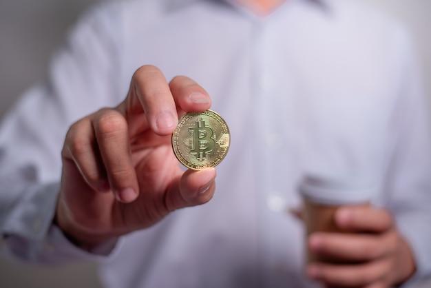 La mano dell'uomo d'affari che tiene un bitcoin d'oro. guadagna con bitcoin, concetto di investimento di denaro in valuta digitale, trasferimento blockchain.
