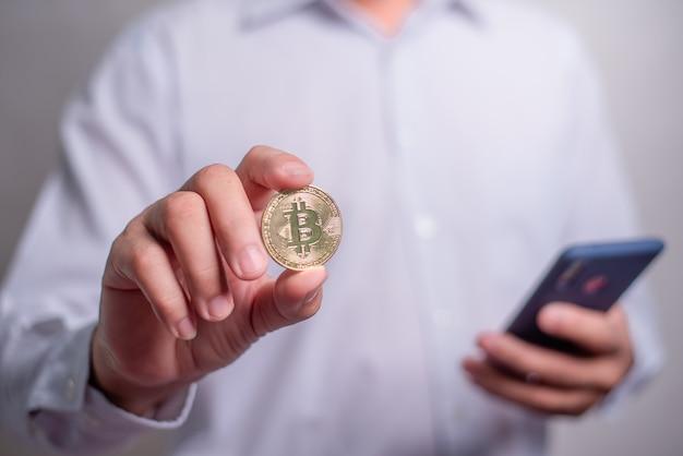 La mano dell'uomo d'affari che tiene un bitcoin d'oro durante l'utilizzo dello smartphone. guadagna con bitcoin, concetto di investimento di denaro in valuta digitale, trasferimento blockchain.