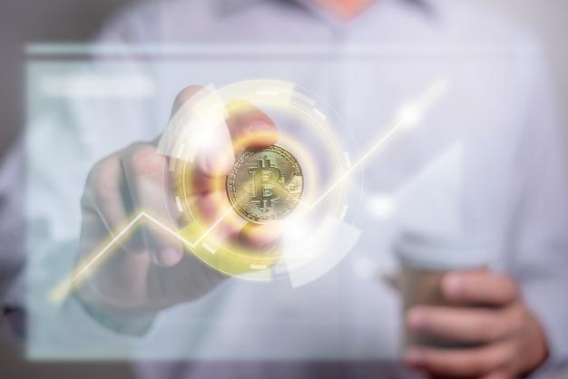 Mano dell'uomo d'affari che tiene un bitcoin d'oro con grafico grafico virtuale. guadagna con bitcoin, concetto di investimento di denaro in valuta digitale, trasferimento blockchain.