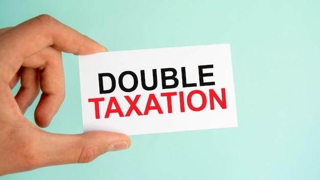 La mano dell'uomo d'affari che tiene il biglietto da visita cartaceo con il testo doppia tassazione, primo piano sfondo azzurro