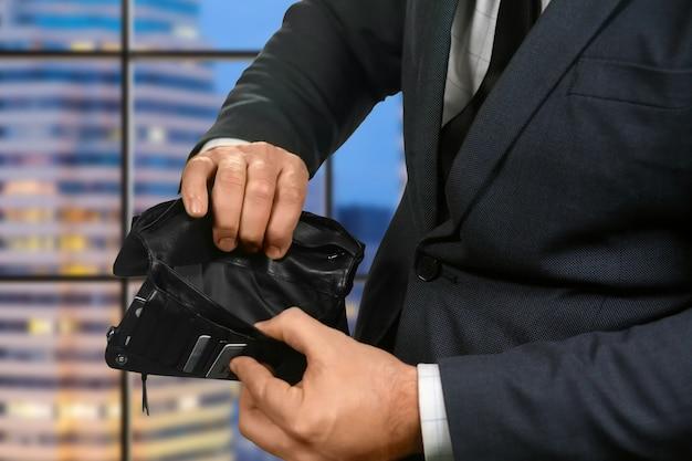 Mani dell'uomo d'affari con portafoglio vuoto. portafoglio vuoto su sfondo serale. sgradevole sorpresa in città. i guai arrivano all'improvviso.