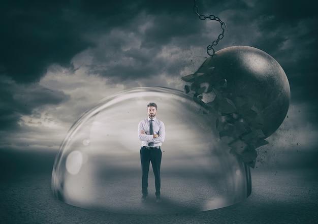 Uomo d'affari in modo sicuro all'interno di una cupola di protezione che lo protegge da una palla da demolizione