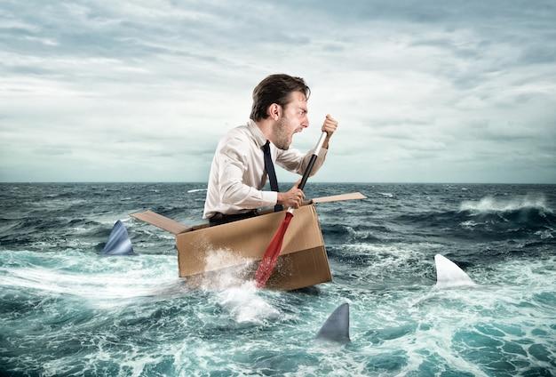 Uomo d'affari che naviga in una scatola di cartone