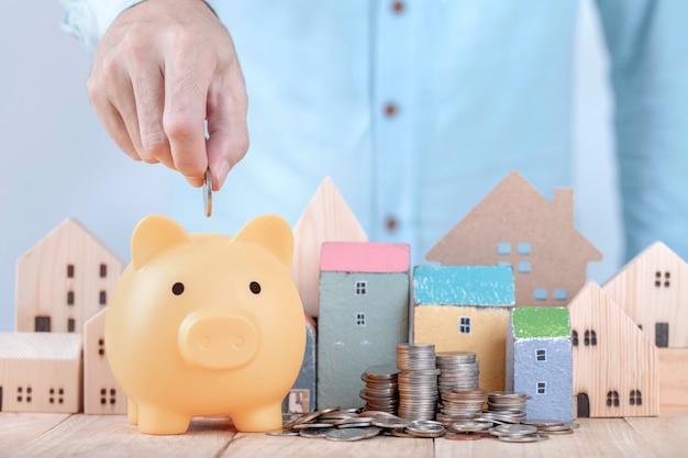 Uomo d'affari risparmiare denaro sul salvadanaio, pianificazione per il futuro dell'affitto per un appartamento o un concetto di casa