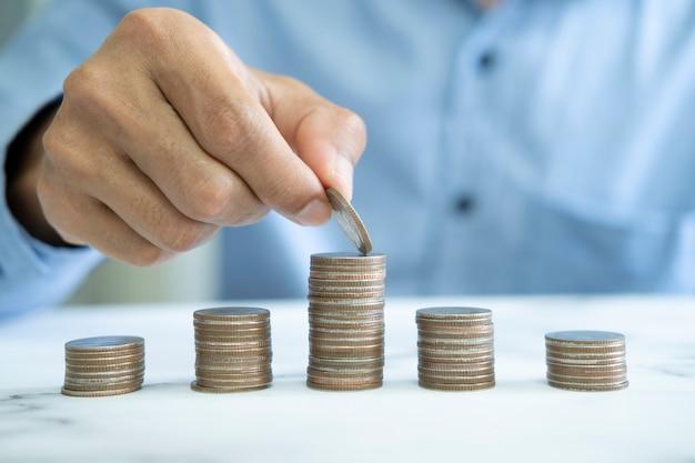 Concetto di risparmio di denaro dell'uomo d'affari. mano che tiene le monete che mettono nel bicchiere della brocca