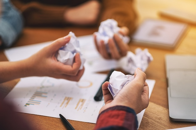 Un uomo d'affari ha rovinato le carte a mano con laptop, tablet e lavoro di carta sul tavolo in una riunione
