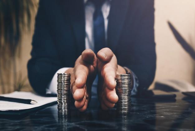 L'uomo d'affari separa le monete dello stack concetto di risparmio e investimento