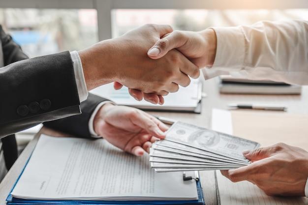 Uomo d'affari che stringe le mani che danno corruzione delle banconote in dollari al direttore aziendale per trattare contratto