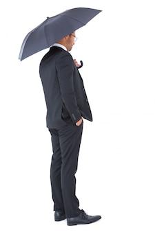 Uomo d'affari che ripara sotto l'ombrello nero