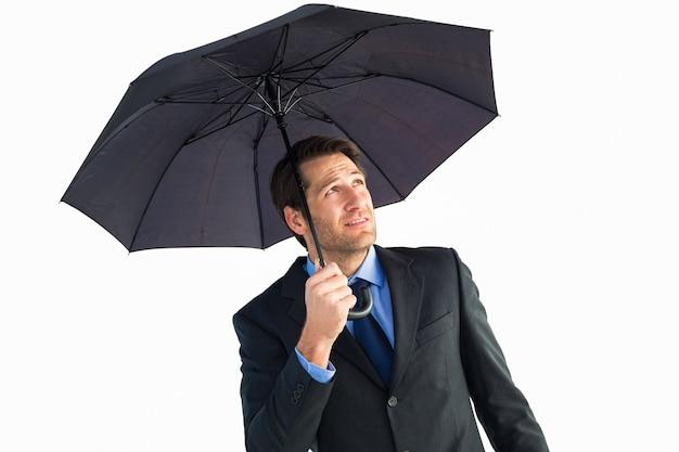 Uomo d'affari che si ripara con l'ombrello nero su fondo bianco