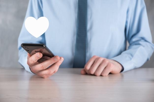 Uomo d'affari in camicia che tiene il simbolo dell'icona del cuore