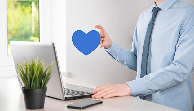 Uomo d'affari in camicia che tiene il cuore come simbolo dell'icona.