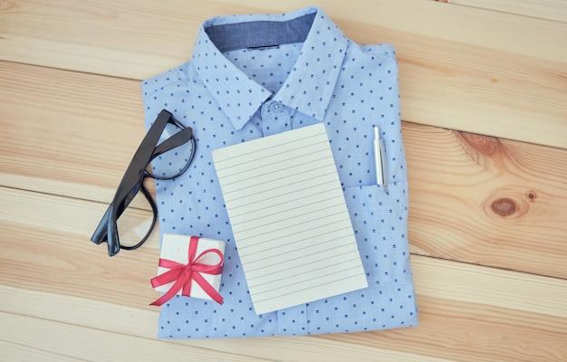 Camicia da uomo d'affari su bianco con blocco note e occhiali su fondo in legno