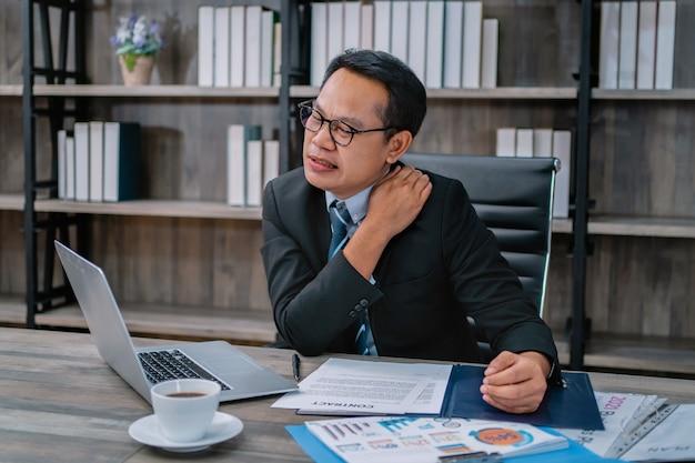 Dolore alla spalla dell'uomo d'affari dal lavoro in ufficio. concetto di assistenza sanitaria