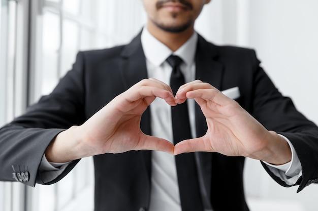 L'uomo d'affari mostra la forma del cuore con la mano.