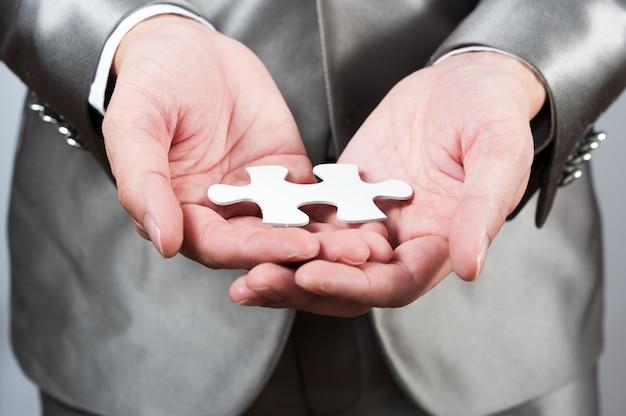 Puzzle bianco di manifestazione dell'uomo d'affari a disposizione, concetto di strategia aziendale
