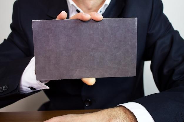 Uomo d'affari che mostra insegna in bianco