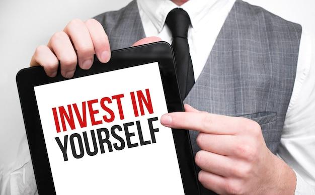 Uomo d'affari che mostra il concetto di business su tablet in piedi in ufficio investire in te stesso