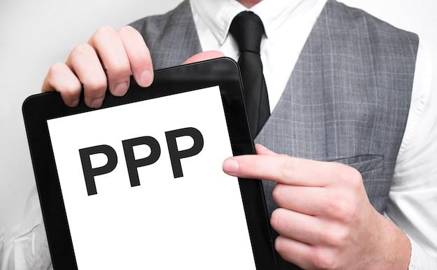 Uomo d'affari che mostra il concetto di business su tablet in piedi in ufficio ppp