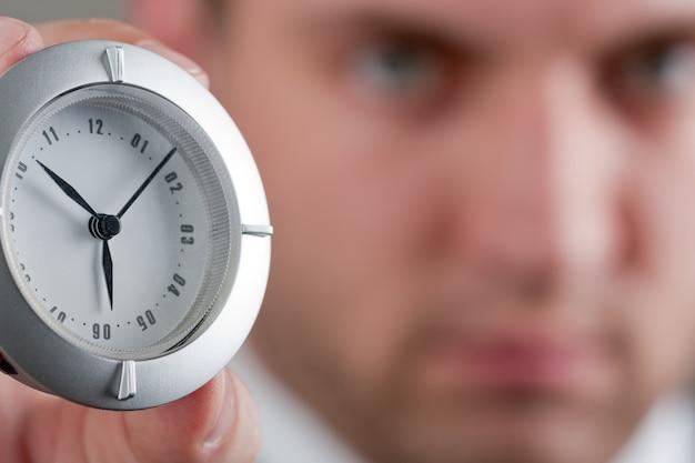 Uomo d'affari che mostra l'orologio per te